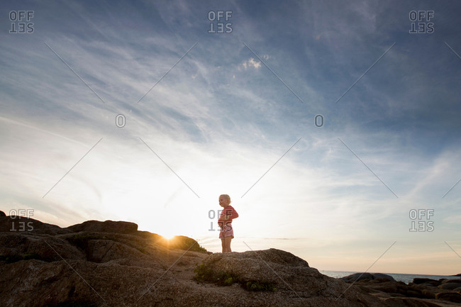 Silhouetted female toddler on coastal rock at sunset, Calvi, Corsica, France