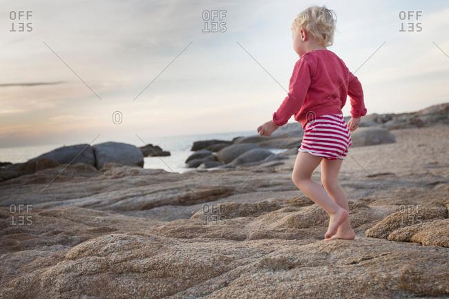 Female toddler toddling on coastal rock, Calvi, Corsica, France