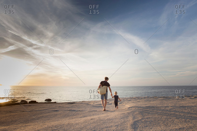 Mature man strolling with his toddler daughter on beach at sunset, Calvi, Corsica, France