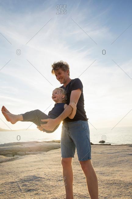 Mature man swinging his toddler daughter on beach, Calvi, Corsica, France