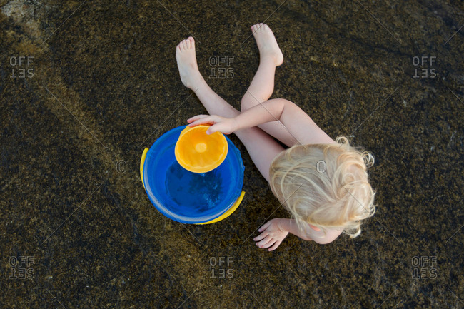 Overhead view of female toddler playing in sand with toy bucket