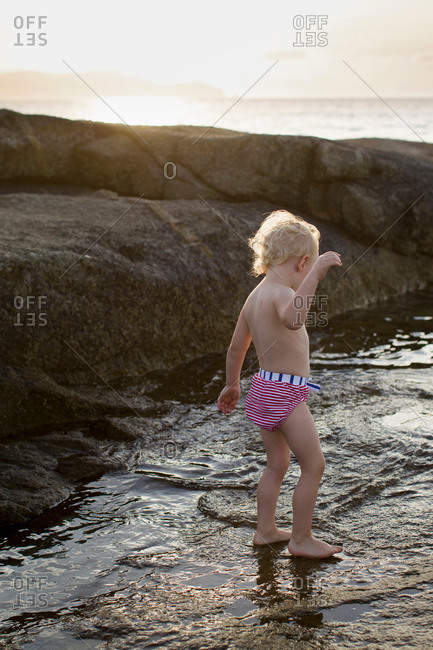 Female toddler paddling in sea, Calvi, Corsica, France