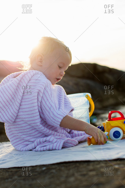 Female toddler sitting on beach playing with toy bucket
