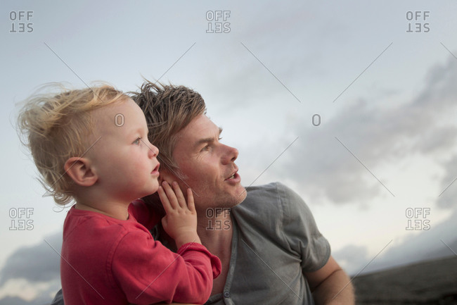 Female toddler and father looking up and watching