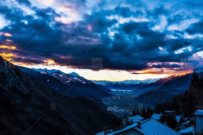 Distant view over snow covered rooftops at dusk, Valtellina, Italy