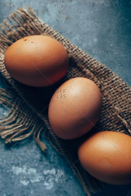 Three free range organic eggs on burlap