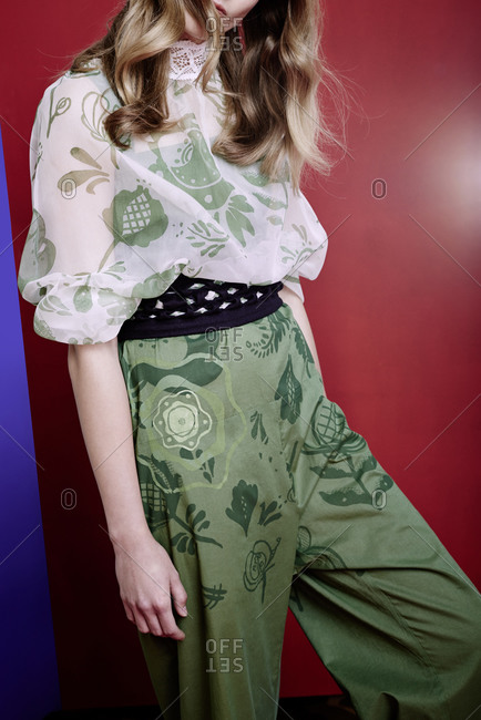 Model wears a wide pants and airy blouse with a floral pattern