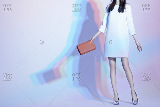 Fashion model with white dress and a red handbag