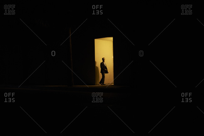 Man walking into a lit doorway in the pitch black night