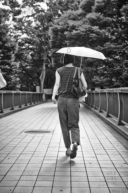 Woman walking on a bridge with an umbrella