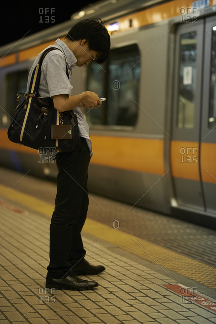 Tokyo, Japan - July 21, 2013: Young man waiting to get on the subway