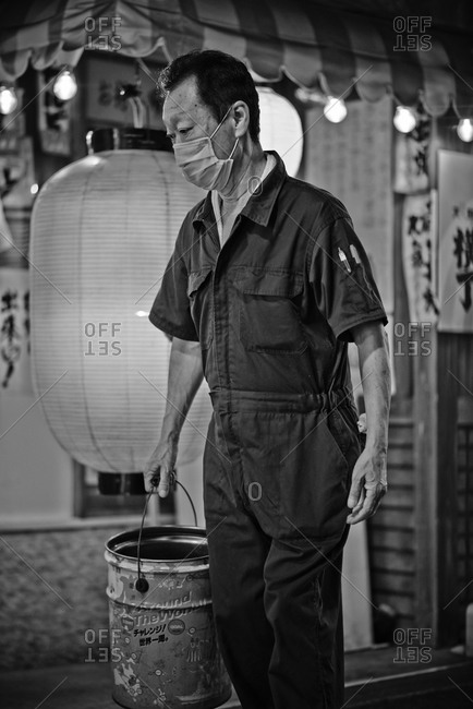 Tokyo, Japan - July 21, 2013: Portrait of an Asian man carrying a bucket