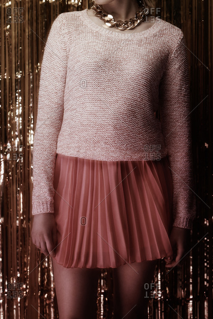 Young woman wearing a pink sweater and pleated skirt