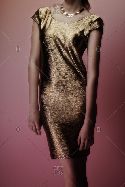 Young woman wearing a gold dress