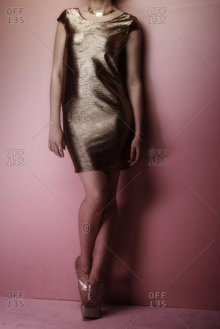 Young woman wearing a gold dress and shoes
