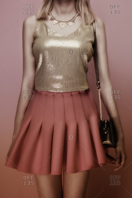 Young woman wearing a pink skirt with gold top