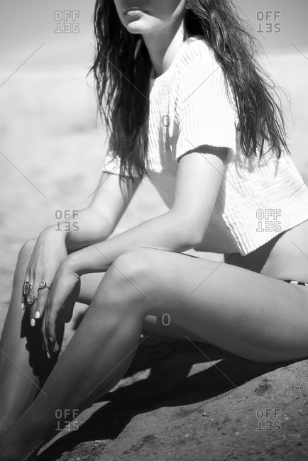 Young model sitting in the sand