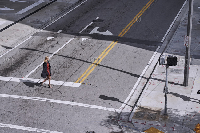 Miami, Florida, USA - November 29, 2014: Woman crossing the street wearing a red and black dress