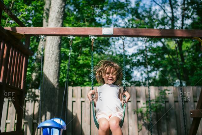Little girl swinging on a backyard swing set