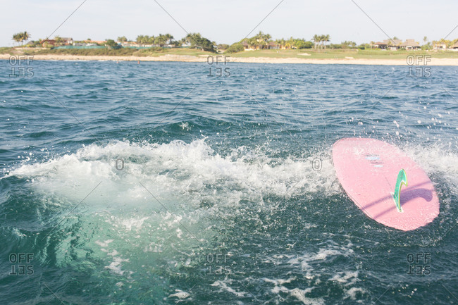 Pink surfboard on surface of water