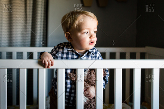 Portrait of a toddler boy standing with stuffed animal in crib