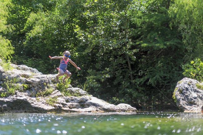 Girl jumping from rock into river