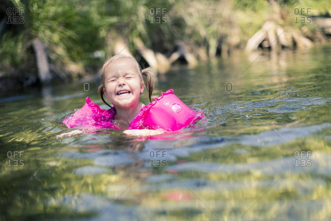 Smiling girl swimming in a river
