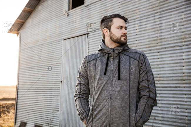 Man by rural building in running jacket