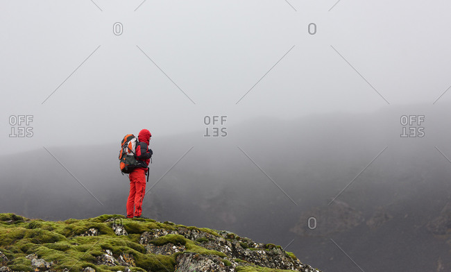 Hiker looking out into a valley on a mossy plateau with dark grey misty clouds in the background