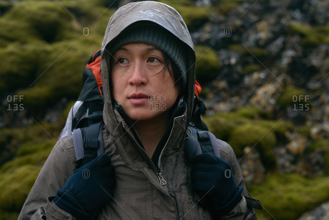 Portrait of an Asian hiker with waterproof gear and backpack in the rain while trekking on an adventure expedition in Iceland