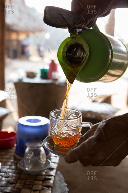 Tea being poured into a small glass mug