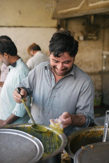 Karachi, Pakistan - February 16, 2016: Man in Pakistan cooking soup