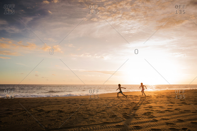 Two young boys frolic on the beach at dusk