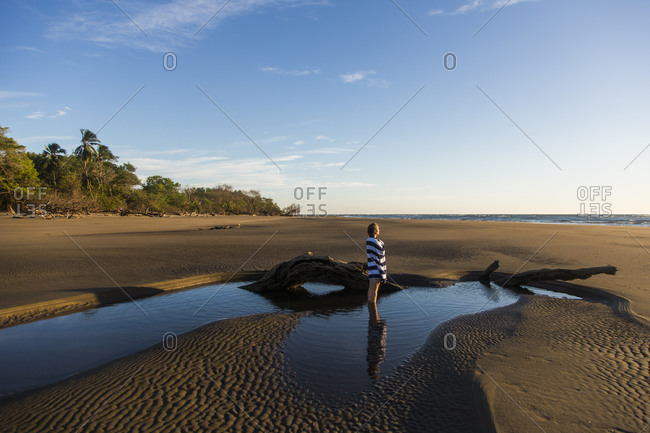 A young woman wrapped in a towel stands on an empty beach in the Padre Ramos Estuary, Nicaragua