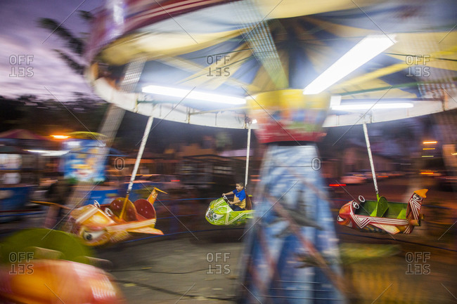 Masaya, Nicaragua - December 8, 2015: A young boy enjoying a ride at an amusement park
