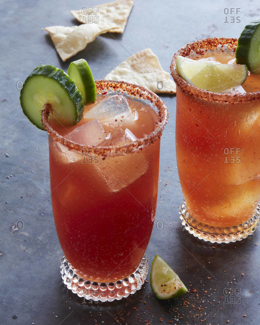Two glasses of Michelada garnished with cucumber and lime