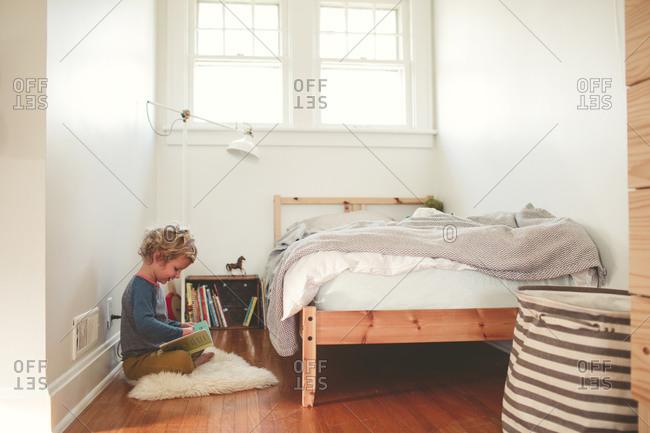 Little boy reading a book on his bedroom floor