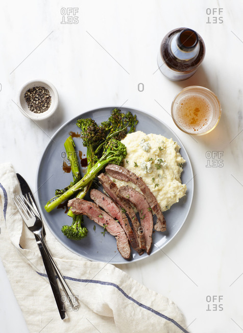 Steak, mashed potatoes and broccolini on a white marble table
