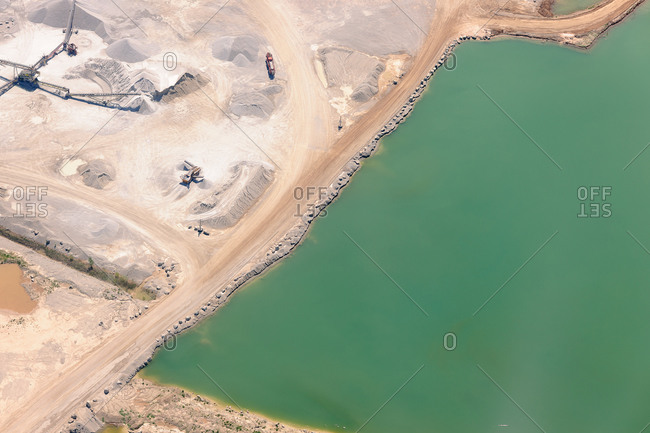 Aerial view of blue-green lake in a gravel quarry