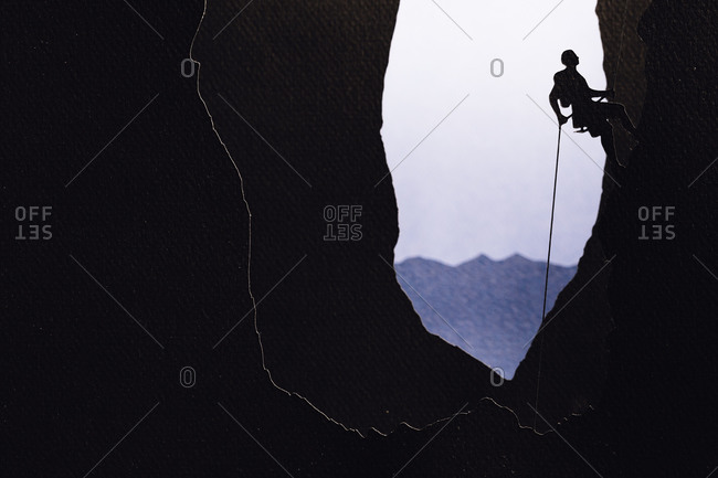 Cardboard cutout of a man rock climbing
