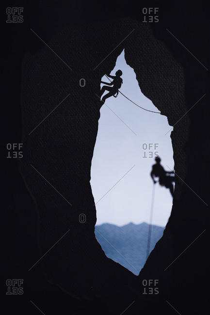 Cardboard cutout of two rock climbers climbing in a cave