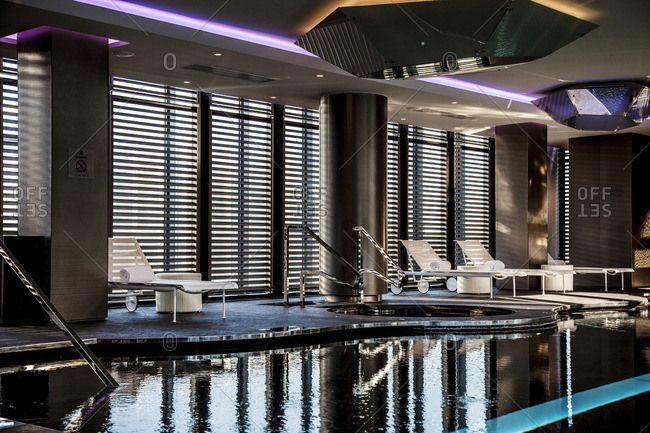 Empty lounge chairs alongside a modern indoor swimming pool and hot tub at the Shiseido Spa, Gallia Hotel, MIlan