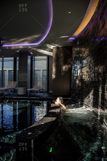 Woman relaxing in a hot tub next to a modern indoor swimming pool at the Shiseido Spa, Gallia Hotel, Milan