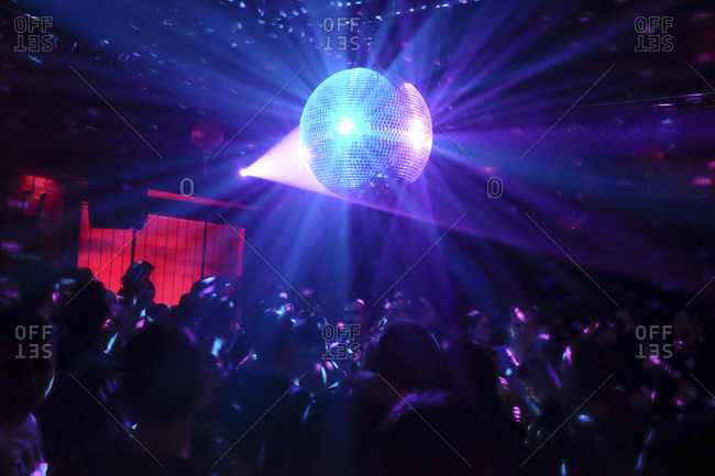 Disco ball and people dancing in a night club