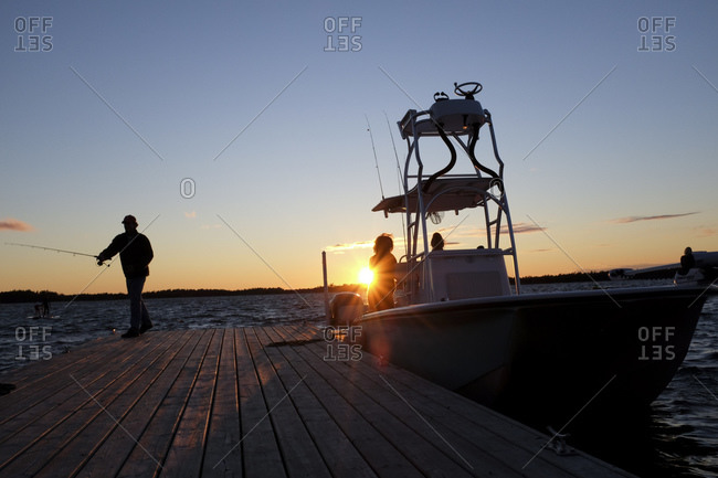Man fishing from a dock at sunset