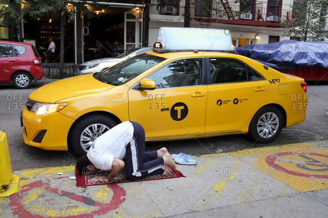 Taxi driver on a prayer rug on a sidewalk beside his vehicle