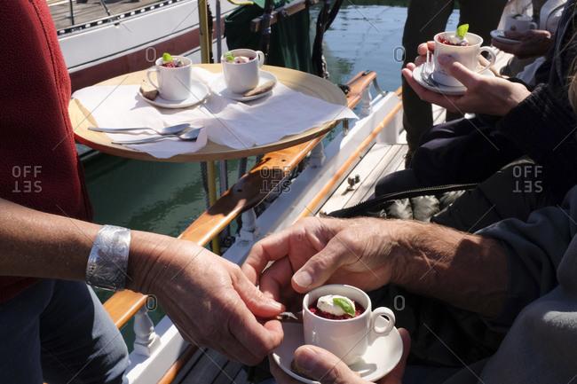 Server handing a fruit dessert to a man