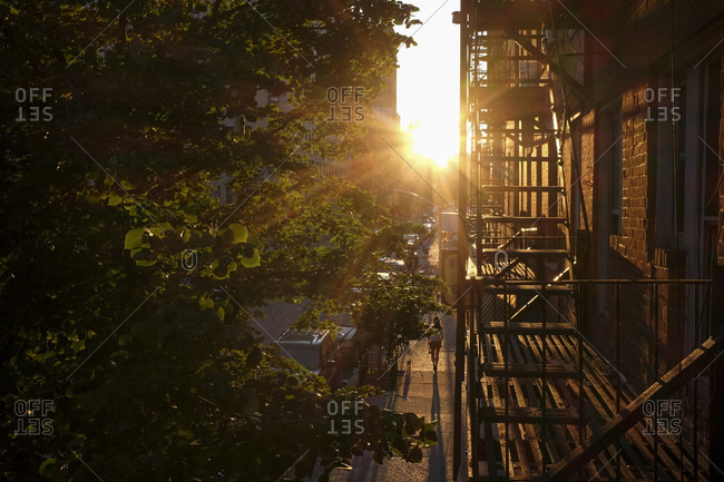 Sun setting over a city street and fire escape