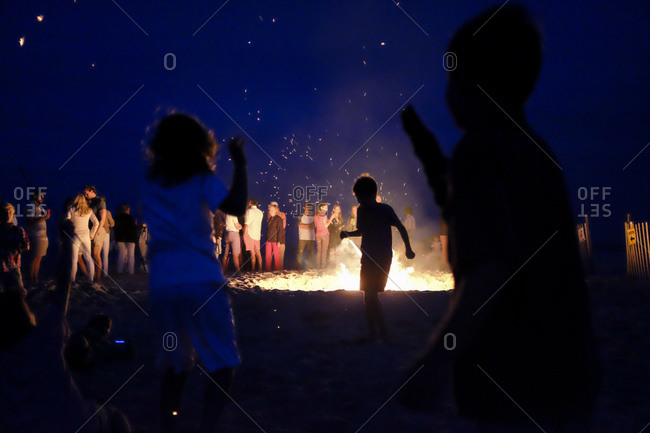 People hanging out around a large bonfire on a beach