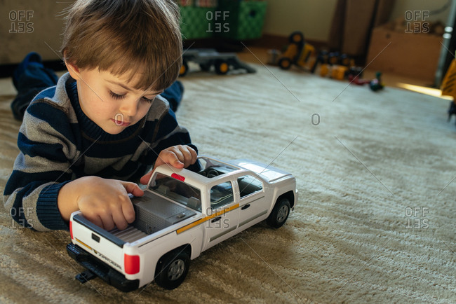 Boy playing with a toy truck on floor